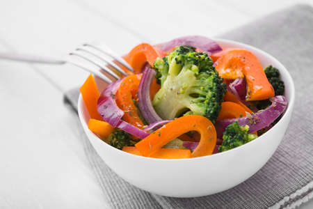 Fresh low-calorie salad with broccoli, pepper and onion on a white wooden table. Diet organic food.