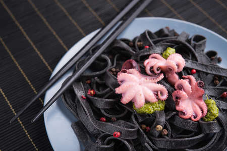 Italian black pasta with cuttlefish ink and marinated octopus on a table. Tasty asian seafood.