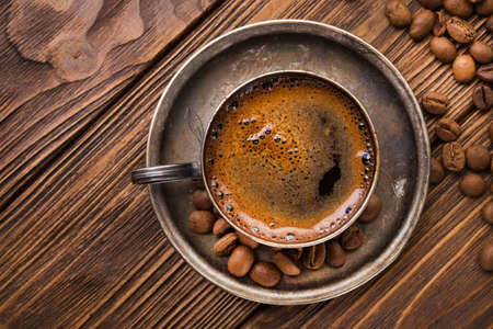 vintage metal coffee cup with roasted beans on a wooden table. top view