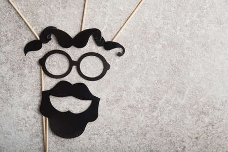 funny faces formed from black photo boots, mustache and glasses on a stone background. concept of holiday father day.