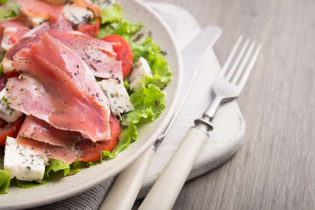 Fresh salad with prosciutto, tomato, lettuce and cheese blue on a stone wooden worktop, close up