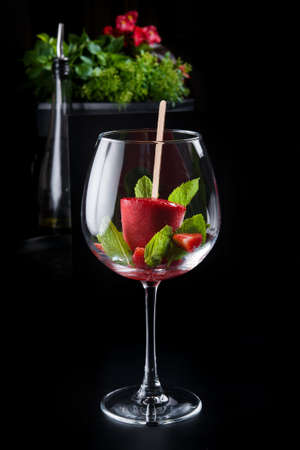 Sparkling wine and a glass of fruit sorbet and mint on a dark table in the restaurant
