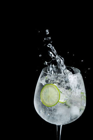 Alcohol drink margarita splash with lime and ice cube on a black background Banque d'images