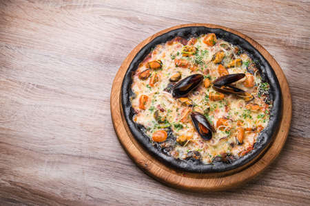 Black pizza with seafood and cheese on a wooden table. top view