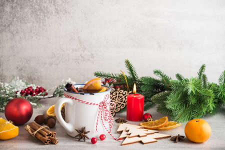 Mulled wine with spices and christmas decoration on a white stone background. New Years holidays concept. Stock Photo