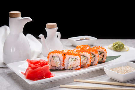 Tasty japan sushi with red ginger, soy sauce and sesame on stone table.