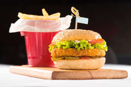 hamburger and french fries on a wooden board isolated on a background