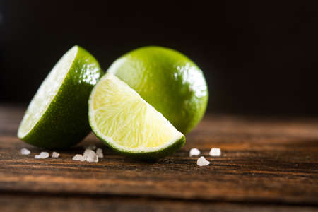 Fresh green lime on a wooden table with salt 版權商用圖片