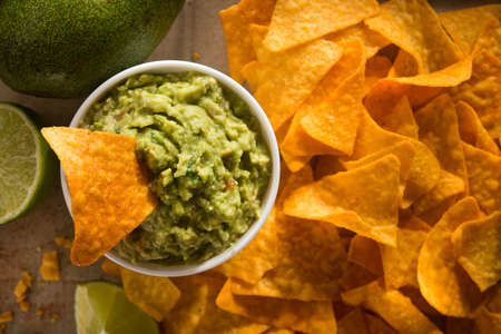 Golden tortilla chips with guacamole on a craft paper