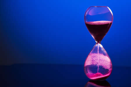 Bright colored pink sand with hourglass on a blue Stock Photo