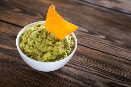 Bowl with guacamole sauce and nachos chips on a wooden table