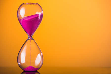 Bright colored time with hourglass on a yellow Imagens