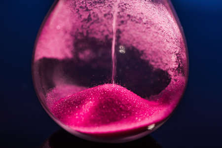 Bright colored pink sand with hourglass Stock Photo