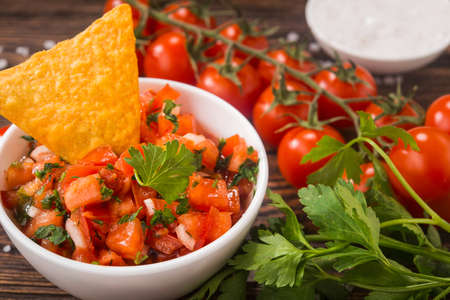 Mexican tomato salsa with tortilla chips on a wooden table