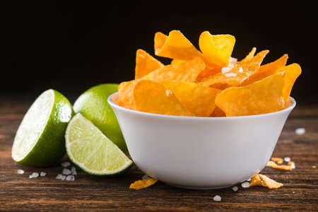 Golden corn nachos chips in a bowl with lime on a wooden table. Фото со стока