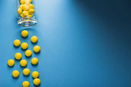 Yellow vitamin pills with bottle on a blue background. top view