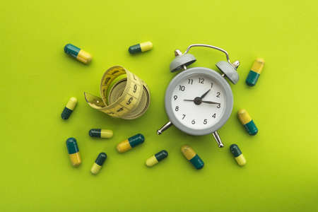 Time for diet and pill treatment on a green background. Diet concept and excess weight. Top or above view.