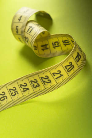 Closeup of yelllow measuring tape on a green background. Diet and weight loss