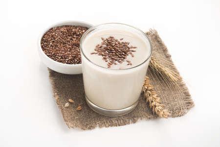 Hafermilch in einem Glas mit Flachskörnern auf weißem Hintergrund bestäubt. Ein nützliches Getränk zum Abnehmen. Diätetische Ernährung. Beliebtes und trendiges Essen.
