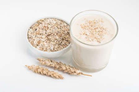 Glass of oat milk and grains in white bowl isolated on white background