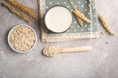 A glass of lean oatmeal milk on a stone background. vegetarian and organic drink food. angle from above.