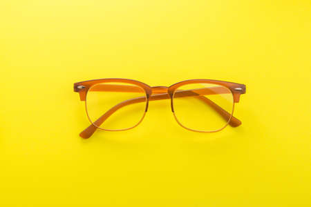 Brown trend glasses on a yellow background. top view Stock Photo