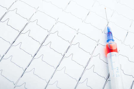 ECG results on paper and red injections to restore heart pulse. Heart attack or hypertension Archivio Fotografico
