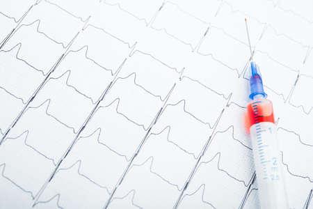 Resultados de ECG en papel e inyecciones rojas para restaurar el pulso cardíaco. Ataque cardíaco o hipertensión Foto de archivo