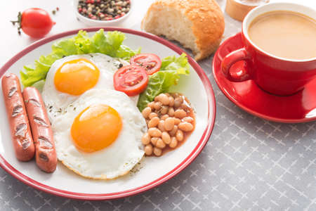 English breakfast with fried egg, beans, tomatoes, sausage, fresh lettuce leaf, coffee cup. Concept of red dishes. Stock Photo