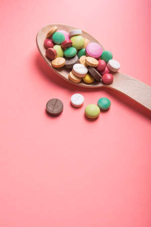 Wooden spoon with medicine pills and tablets on a pastel pink background Imagens