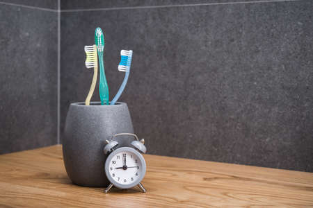 Toothbrush in holder with clock. Concept of cleaning and care of the teeth in a scandinavian bathroom. oral hygiene. concept of dental care.