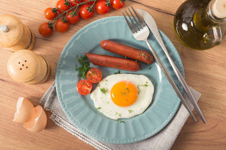 Pyszne śniadanie składające się z jajek sadzonych, kiełbasek wieprzowych i świeżych pomidorów na kuchennym stole. Zdjęcie Seryjne