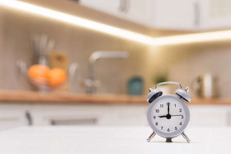 Selected focus on gray alarm clock on a kithen white wooden table. Time for breakfast, 9 o'clock in the morning.