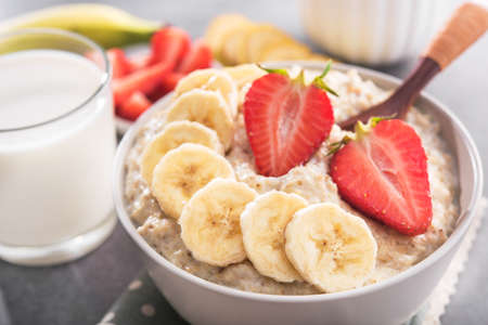 Oatmeal bowl with banana and strawberry, milk glass in a stone table. healthy organic food.