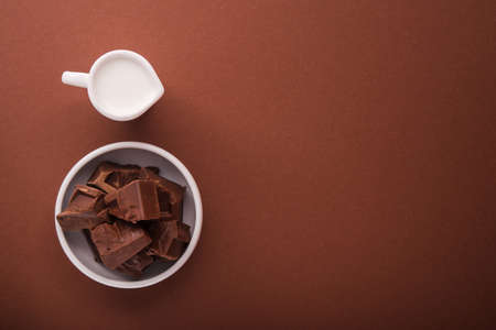Pieces of chocolate and a carafe of milk on a brown color background. Top view. place for text