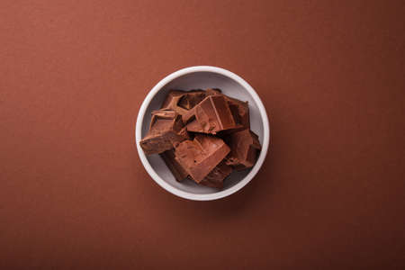 Pieces of chocolate in a white bowl on brown color background. Top view. Stock Photo