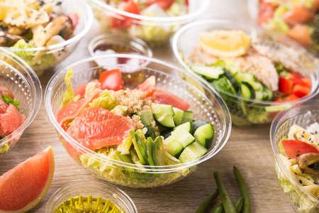 Conteneur à emporter en plastique avec salade fraîche se compose de concombre, avocat, tomate, pamplemousse, sur un fond en bois. Nourriture savoureuse pour le déjeuner.