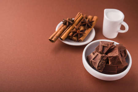 Pieces of chocolate and spices cinnamon, badian on white bowl on a color brown background.
