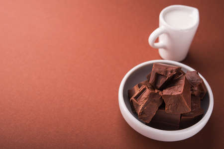 Pieces of chocolate and a carafe of milk on a brown color background. place for text Stock Photo