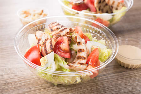 Plastic take away container with fresh salad on a wooden background. 스톡 콘텐츠