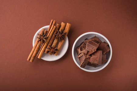 Pieces of chocolate and spices cinnamon, badian on white bowl on a color brown background. Top view. Stock Photo