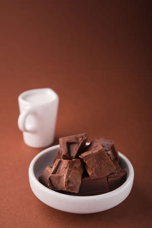 Pieces of chocolate and a carafe of milk on a brown color background Stock Photo