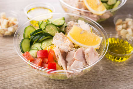 Plastic take away container with fresh salad on a wooden background. Standard-Bild