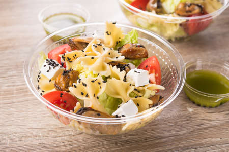 Conteneur à emporter en plastique avec salade fraîche (moules, fromage feta, pâtes, tomate) sur une table en bois. Banque d'images