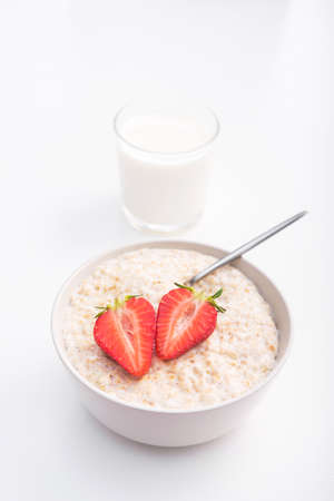 Sweet porridge with red strawberry and glass of milk. healthy morning breakfast. Banco de Imagens