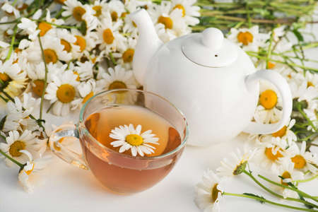 Glass cup with herbal tea with chamomile flowers on a white background. Healthy drink.