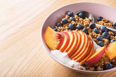 Bowl of granola with yogurt, peach slices and bluberry on a wooden table. Morning food dessert. Healthy breakfast. copy space