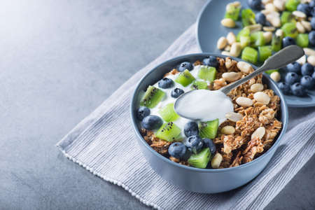 Healthy breakfast with granola cereal with blueberry, kiwi, yogurt and peanuts in blue bowl on a stone. Morning sweet dessert snack.