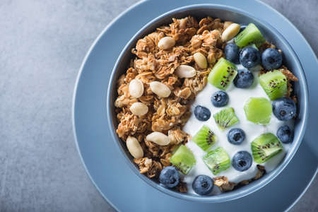 Healthy breakfast with granola cereal with blueberry, kiwi, yogurt and peanuts in blue bowl on a stone. Morning sweet dessert snack. top view 写真素材