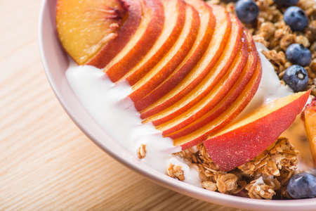 Bowl of granola with yogurt, peach slices and bluberry on a wooden table. Morning food dessert. Healthy breakfast. 写真素材